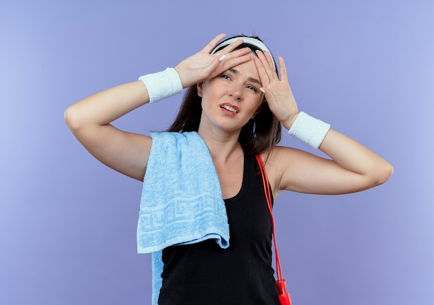 파란색 벽 위에 서있는 운동 후 피곤하고 지쳐 보이는 그녀의 어깨에 수건으로 머리띠에 젊은 피트 니스 여자