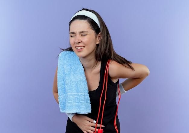彼女の肩にタオルを持ったヘッドバンドの若いフィットネス女性は、青い背景の上に立っている痛みを感じて背中に触れて気分が悪いように見えます
