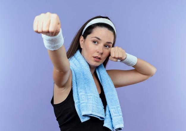 彼女の肩にタオルを持ったヘッドバンドの若いフィットネス女性は、青い背景の上に自信を持って立っているように見えるくいしばられた握りこぶしでああ運動選手のようにポーズをとる