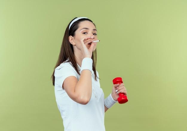 Молодая фитнес-женщина в головной повязке тренируется с гантелями и курит сигарету, стоя над светлой стеной