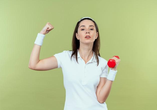 明るい壁の上に立っている深刻な顔で上腕二頭筋を示すダンベルで運動しているヘッドバンドの若いフィットネス女性
