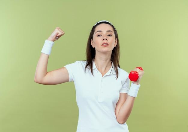 明るい壁の上に立っている深刻な顔で上腕二頭筋を示すダンベルでワークアウトヘッドバンドの若いフィットネス女性