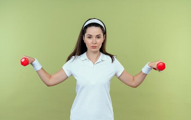 明るい背景の上に立って自信を持って見えるダンベルでワークアウトヘッドバンドの若いフィットネス女性