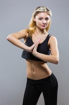 Молодая женщина фитнеса в спортивном стиле стоя на белом фоне. изолированные