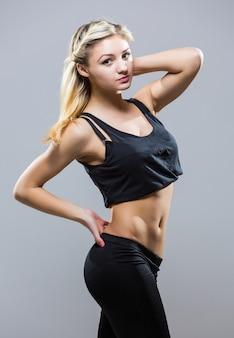 白い背景に立っているスポーツスタイルの若いフィットネス女性。孤立