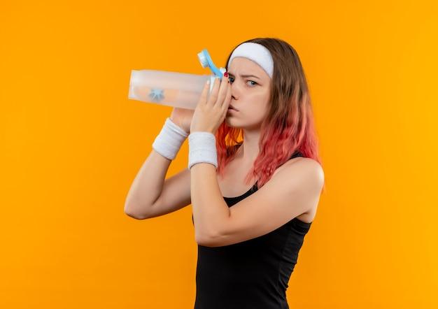 オレンジ色の壁の上に立っている深刻な顔と水を飲むスポーツウェアの若いフィットネス女性