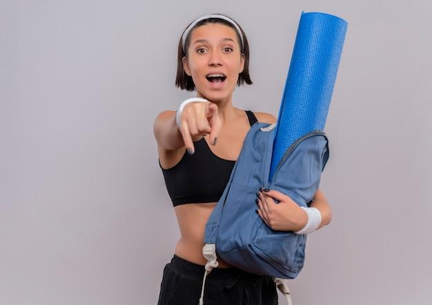 Молодая фитнес-женщина в спортивной одежде, держащая рюкзак с ковриком для йоги, счастливая и удивленная, указывая указателем на камеру, стоящую над белой стеной