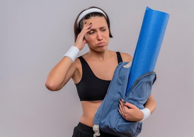 Молодая фитнес-женщина в спортивной одежде, держащая рюкзак с ковриком для йоги, выглядит смущенной и очень взволнованной с грустным выражением лица, стоящего над белой стеной