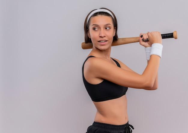 白い壁の上に立って笑顔で自信を持って表情を脇に見て野球のバットを保持しているスポーツウェアの若いフィットネス女性
