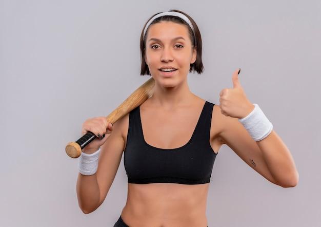 야구 방망이를 들고 운동복에 젊은 피트 니스 여자 흰 벽 위에 서 서 자신감을 보여주는 엄지 손가락 미소