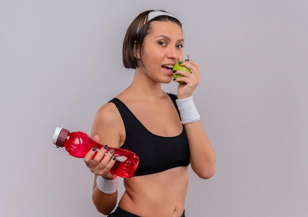 水のボトルと白い壁の上に立っている噛むリンゴを笑顔の青リンゴを保持しているスポーツウェアの若いフィットネス女性