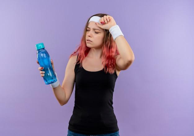 紫色の壁の上に立って疲れているように見える水のボトルを保持しているスポーツウェアの若いフィットネス女性