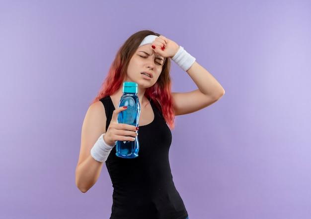 紫色の壁の上に立っている強い頭痛を持っている体調不良に見える水のボトルを保持しているスポーツウェアの若いフィットネス女性