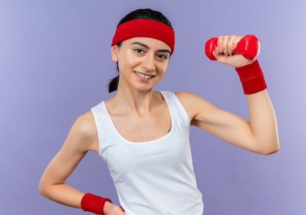 紫色の壁の上に元気に立って笑顔の拳を上げるカメラのポーズをとってダンベルを保持しているスポーツウェアの若いフィットネス女性