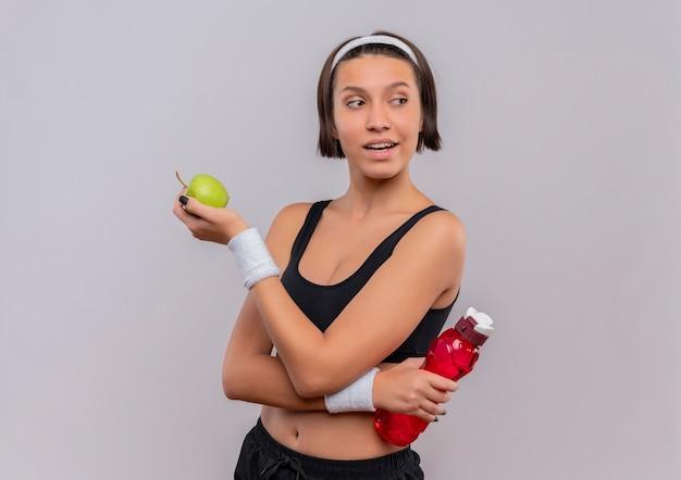 Молодая фитнес-женщина в спортивной одежде держит зеленое яблоко и бутылку воды, глядя в сторону с уверенной улыбкой, стоя над белой стеной