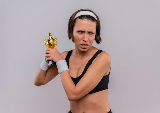 Молодая фитнес-женщина в спортивной одежде держит свой трофей, глядя в сторону с хмурым лицом, стоящим над белой стеной
