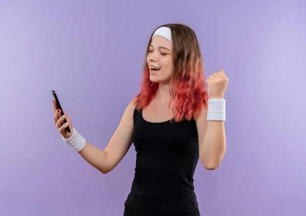 Молодая фитнес-женщина в спортивной одежде, держащая смартфон, сжимая кулак, счастлива и вышла, стоя над фиолетовой стеной