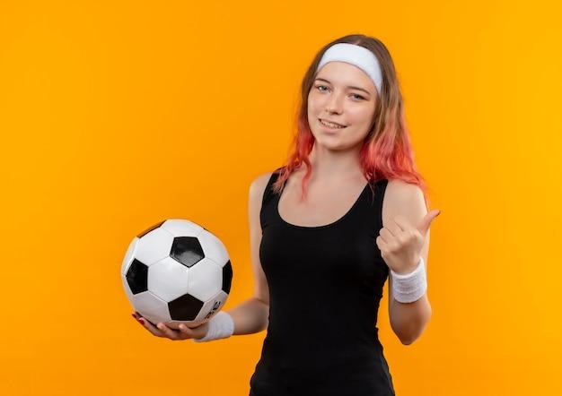 오렌지 벽 위에 서 엄지 손가락을 보여주는 행복 한 얼굴로 웃 고 축구 공을 들고 운동복에 젊은 피트 니스 여자
