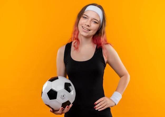 Молодая фитнес-женщина в спортивной одежде держит футбольный мяч со счастливым лицом, весело улыбаясь, стоя над оранжевой стеной