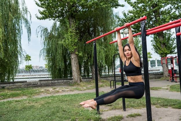 完璧な体のために鉄棒でエクササイズを行うスポーツウェアの若いフィットネス女性。健康的な生活様式