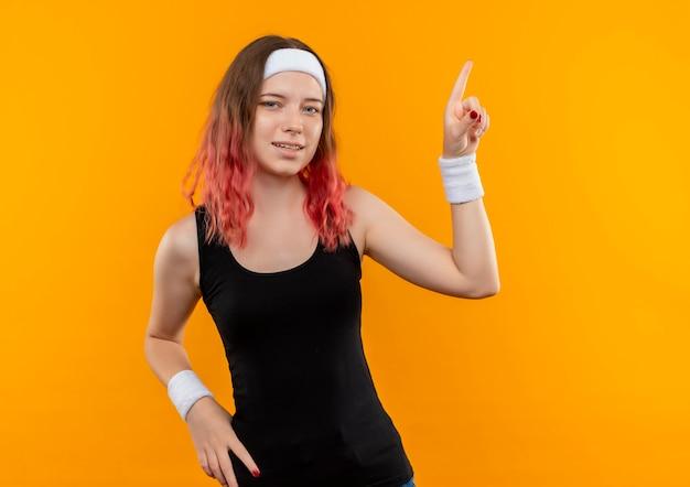 오렌지 벽 위에 서있는 측면을 손가락으로 가리키는 운동복에 젊은 피트 니스 여자