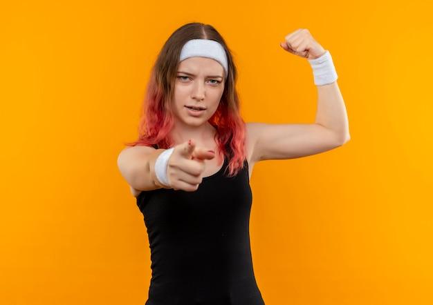 오렌지 벽 위에 서있는 카메라에 검지 손가락으로 자신감을 가리키는 찾고 주먹을 올리는 운동복에 젊은 피트 니스 여자