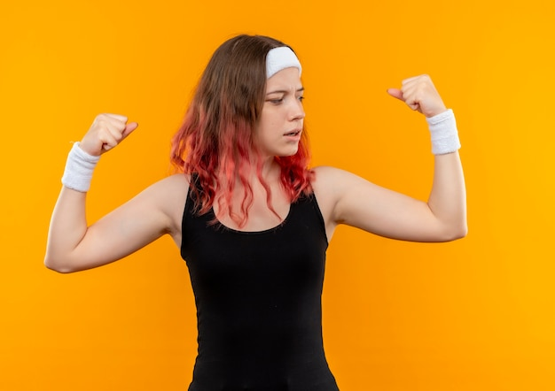 Молодая фитнес-женщина в спортивной одежде, поднимая кулаки, показывая бицепс, уверенно глядя, стоя над оранжевой стеной