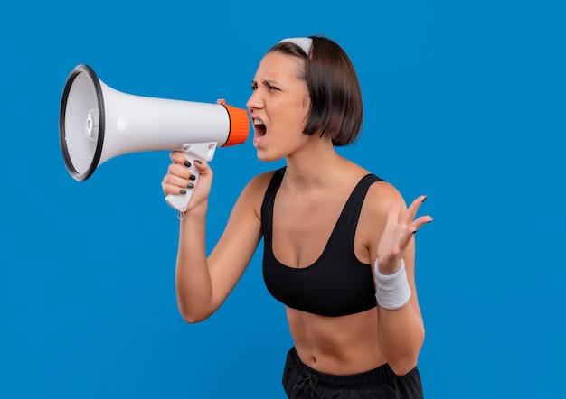 Молодая фитнес-женщина в спортивной одежде кричит в мегафон с агрессивным выражением лица, стоя у синей стены