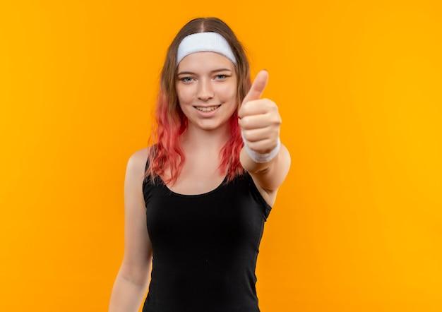 주황색 벽 위에 서있는 엄지 손가락을 유쾌하게 보여주는 운동복에 젊은 피트 니스 여자