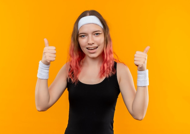 주황색 벽 위에 서있는 양손으로 엄지 손가락을 유쾌하게 보여주는 운동복에 젊은 피트 니스 여자