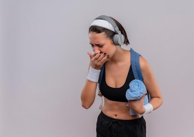흰색 벽 위에 서있는 몸이 기침을 찾고 수건을 들고 머리에 배낭과 헤드폰 스포츠웨어에 젊은 피트 니스 여자