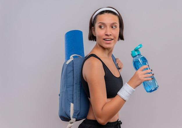 白い壁の上に立っている顔に笑顔で脇を見て水のボトルを保持しているバックパックとヨガマットとスポーツウェアの若いフィットネス女性