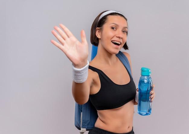 배낭과 요가 매트와 함께 운동복에 젊은 피트 니스 여자 물 한 병을 들고 웃 고 흰 벽 위에 서 손으로 흔들며 웃 고