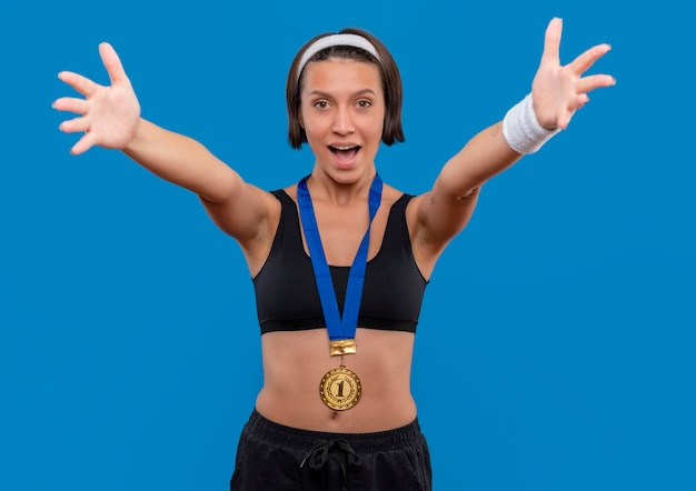 彼女の首の周りに金メダルを持っているスポーツウェアの若いフィットネス女性は、青い壁の上に立って歓迎のジェスチャーを大きく開く手を作ります