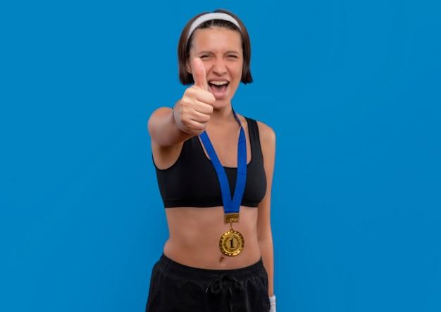 파란색 벽 위에 그녀의 성공 행복하고 흥분된 서 기쁨 엄지 손가락을 보여주는 그녀의 목 주위에 금메달과 운동복에 젊은 피트 니스 여자