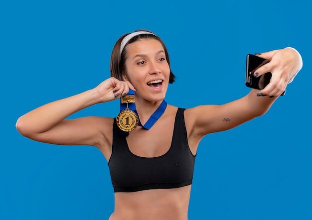 青い壁の上に立っている彼女のスマートフォンのカメラにメダルを示す自分撮りを取っている彼女の首の周りに金メダルを持つスポーツウェアの若いフィットネス女性