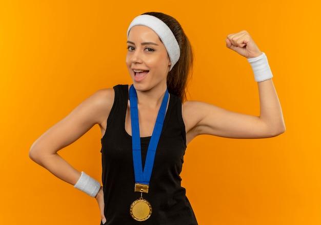 오렌지 벽 위에 행복하고 긍정적 인 미소를 주먹을 올리는 그녀의 목 주위에 머리띠와 금메달 운동복에 젊은 피트 니스 여자