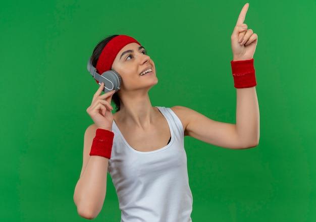 Молодая фитнес-женщина в спортивной одежде с повязкой на голову и наушниками, весело улыбаясь, указывая вверх указательным пальцем, стоящим над зеленой стеной