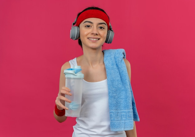 ピンクの壁の上に立って自信を持って笑顔の水のボトルを保持している彼女の肩にタオルとヘッドバンドとヘッドフォンでスポーツウェアの若いフィットネス女性