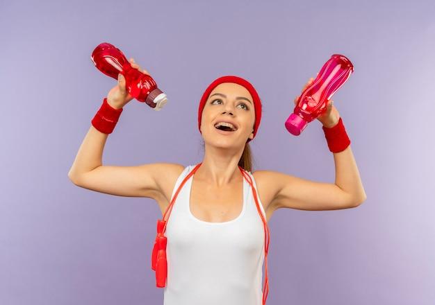 Молодая фитнес-женщина в спортивной одежде с повязкой на голову и скакалкой на шее держит бутылки с водой, глядя вверх счастливой и веселой, стоя над серой стеной