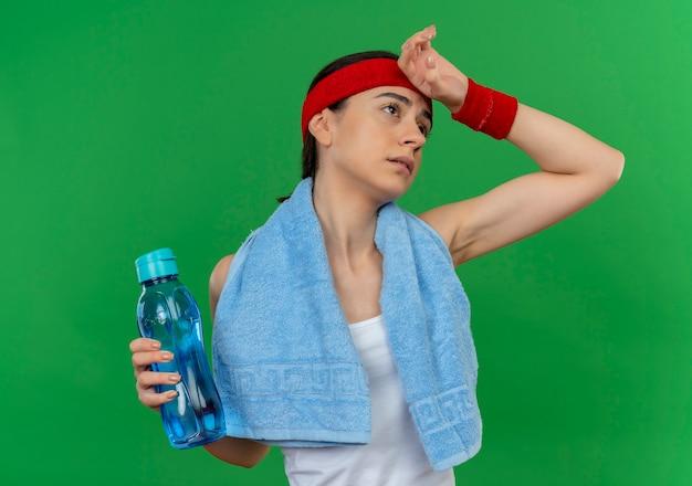 Молодая фитнес-женщина в спортивной одежде с повязкой на голову и полотенцем на шее, держащая бутылку воды, выглядит усталой и измученной, стоя у зеленой стены