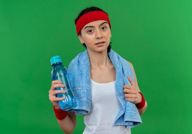緑の壁の上に立って疲れているように見える水のボトルを保持している彼女の首にヘッドバンドとタオルでスポーツウェアの若いフィットネス女性