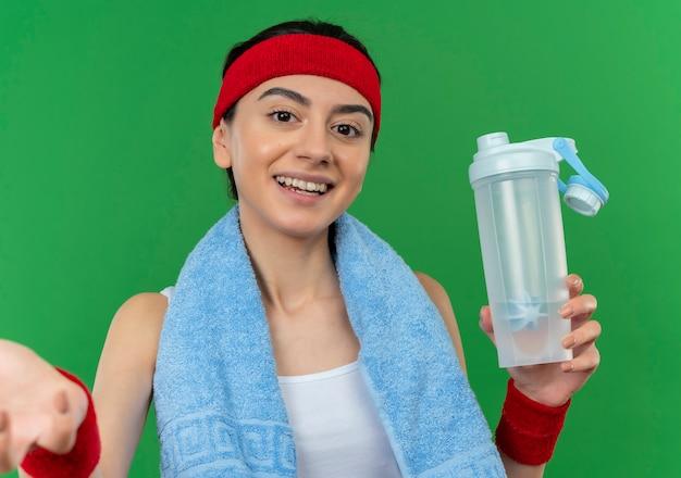 緑の壁の上に元気に立って笑顔の水のボトルを保持している彼女の首にヘッドバンドとタオルでスポーツウェアの若いフィットネス女性