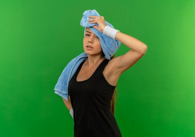 녹색 벽 위에 피곤하고 지친 찾고 그녀의 목에 머리띠와 수건 스포츠웨어에 젊은 피트 니스 여자