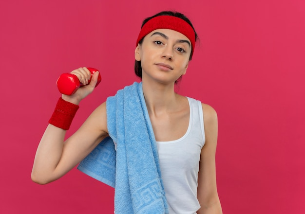 ピンクの壁の上に立って自信を持って見える上げられた手でダンベルを保持している彼女の肩にヘッドバンドとタオルを持つスポーツウェアの若いフィットネス女性