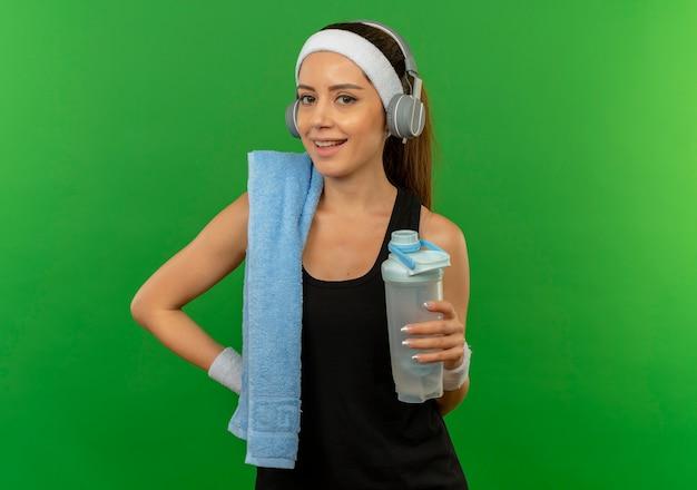 緑の壁の上に元気に立って笑っている水のボトルを保持している彼女の肩にヘッドバンドとタオルでスポーツウェアの若いフィットネス女性