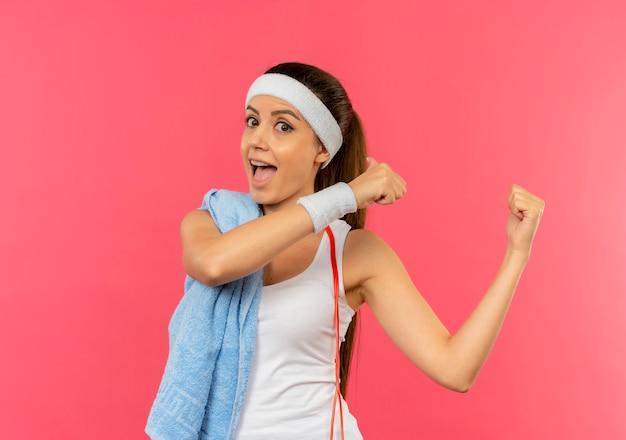 ピンクの壁の上に元気に立って笑顔を後ろに向けて肩にヘッドバンドとタオルを持ったスポーツウェアの若いフィットネス女性