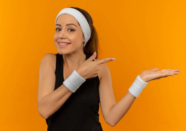 Молодая фитнес-женщина в спортивной одежде с повязкой на голову счастлива и позитивна, указывая руками и пальцем в сторону, стоя над оранжевой стеной