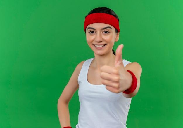 머리띠 행복하고 긍정적 인 웃고 녹색 벽 위에 서 엄지 손가락을 유쾌하게 보여주는 운동복에 젊은 피트 니스 여자