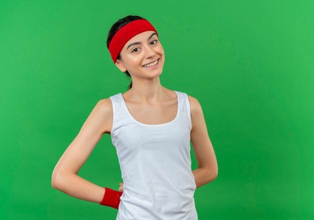 머리띠 행복하고 긍정적 인 녹색 벽 위에 유쾌하게 서있는 스포츠웨어에 젊은 피트 니스 여자